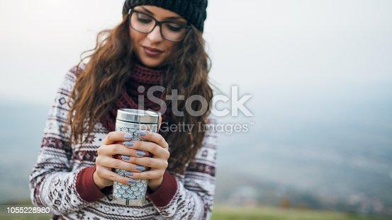 Young woman holding warm cup of tea