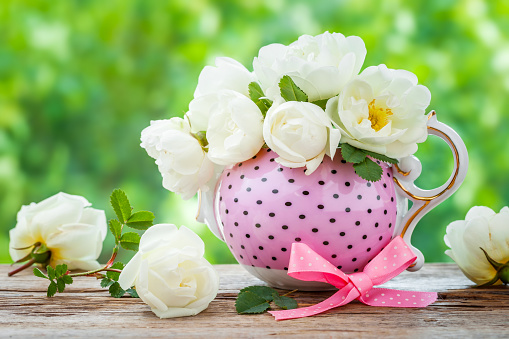 Tea kettle and bouquet of roses.