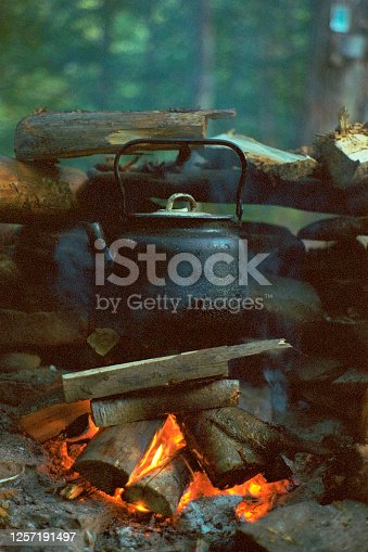Close up of tea kettle on bonfire in forest