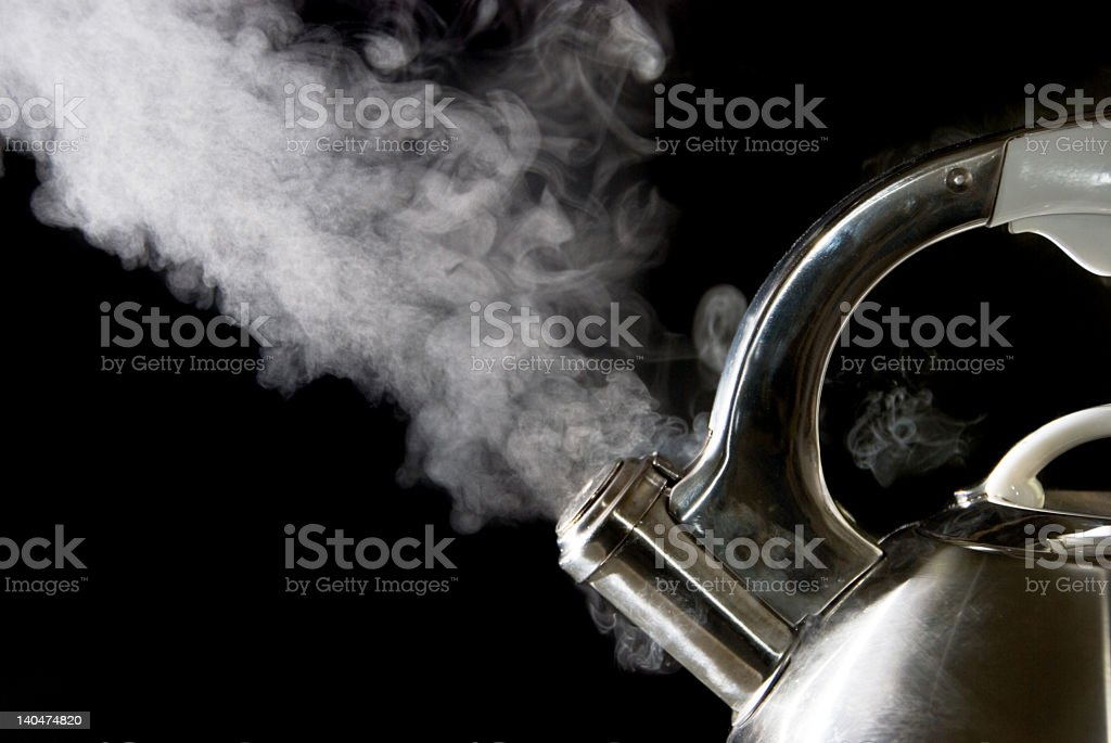 Tea kettle releases steam and boils water on black backdrop stock photo