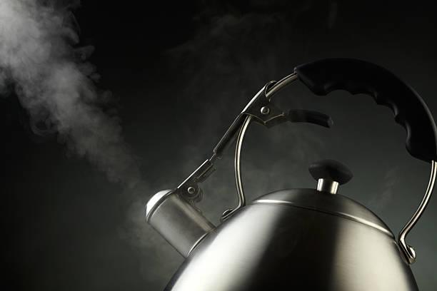 Tetera con agua hirviendo sobre fondo oscuro - foto de stock