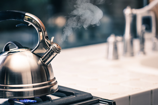 Tea Kettle with Steam on top of a stove