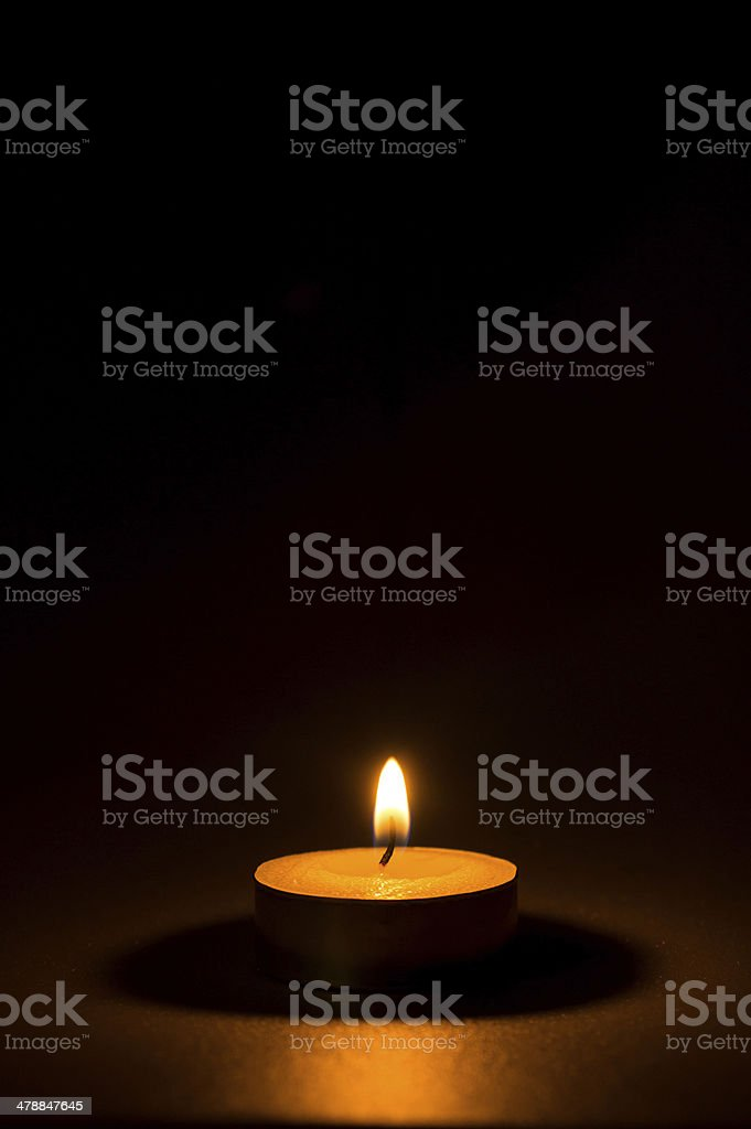 Tea light candle on black background stock photo