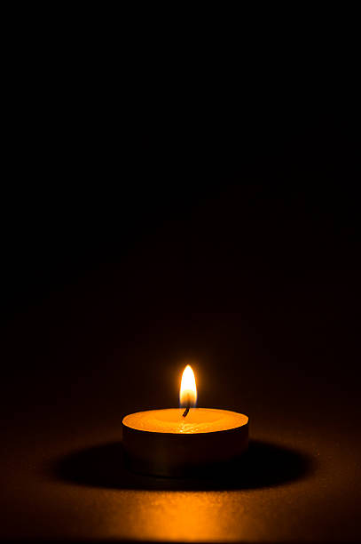 Tea light candle on black background stock photo