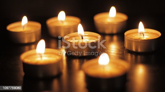 Group of tea candles burning on a black reflective surface