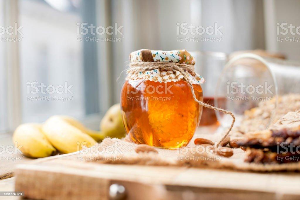 thee, noten, honing, in een pot en een banaan op een houten tafel in de buurt van het oog. Gezond ontbijt. Vintage foto. - Royalty-free Amandel - Noot Stockfoto
