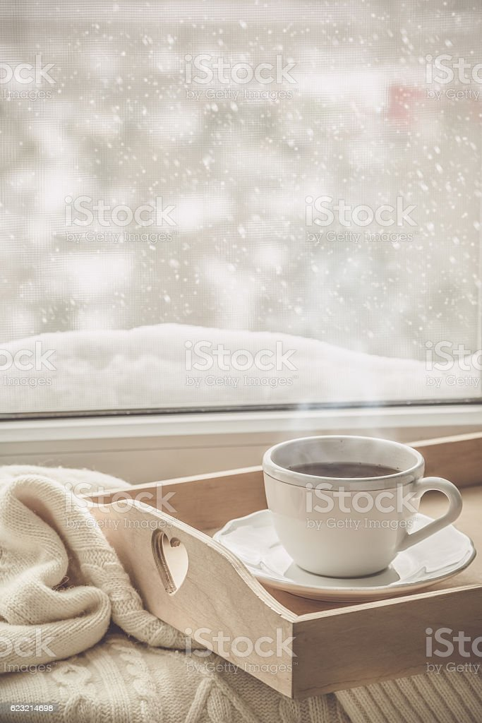 Tea on tray and sweater in from of snowing winter stock photo