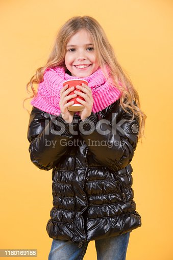 Tea or coffee take away. Child smile with red cup on orange background. Warm up drink. Autumn season concept. Girl with long blond hair in black jacket hold mug.