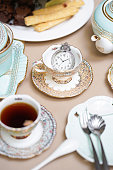 Tea party. Tea time served in the morning with different kind of pastries on the background. Selective focus on the vintage pocket watch.