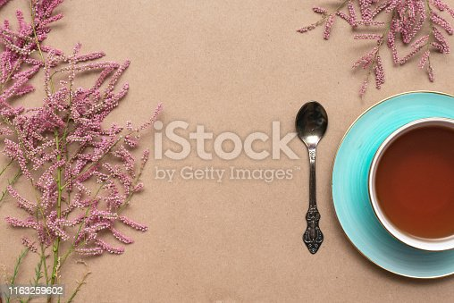 Cup of hot tea and a tamarix gallica tree branches on a brown background.