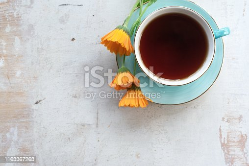 Cup of hot tea on a white wooden table background.