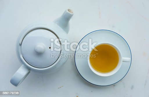 Tea pot and cup of tea on white marble desk