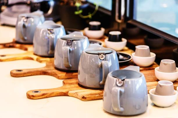Tea Pots Many tea pots are assembled in a display row on wooden chopping boards in the window of a cafe tea room stock pictures, royalty-free photos & images