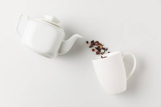 tea pouring from pot into cup stock photo