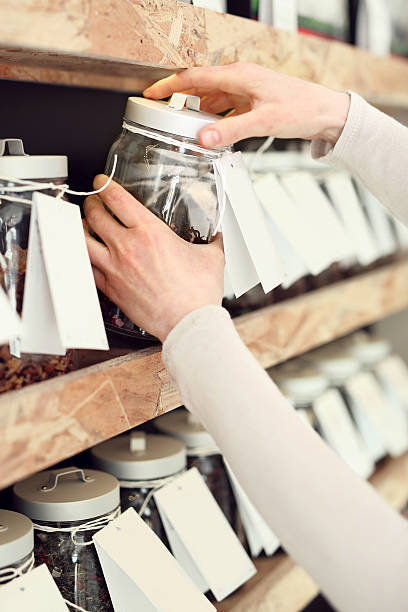 Tea room, a woman buys fruit tea Woman chooses a drink while shopping in a store tea tea room stock pictures, royalty-free photos & images