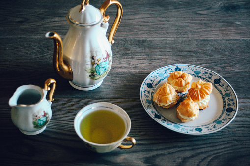 Tea set and cream puffs on wooden background