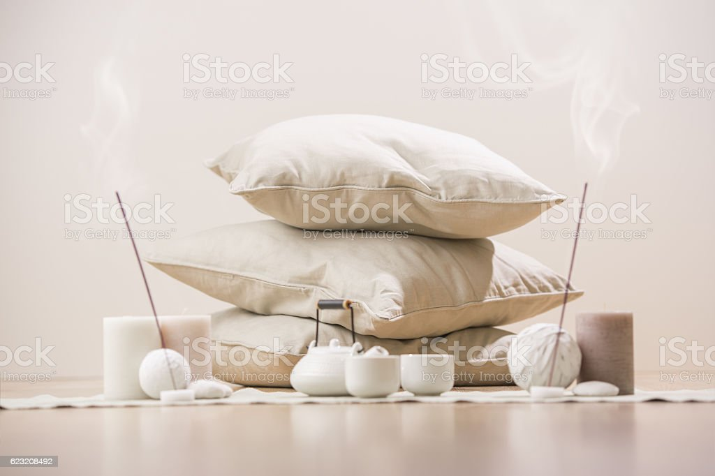 Tea set with incense sticks and candles with pillows stock photo