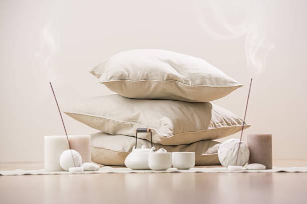 tea set with incense sticks and candles with pillows - meditationsräume stock-fotos und bilder