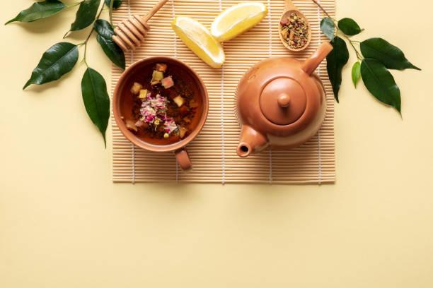 cadre de thé avec tasse, théière, citron, cuillère de thé séché et branche verte avec des feuilles sur le tapis de bambou sur fond jaune. vue de dessus, composition de lay plat - cérémonie photos et images de collection