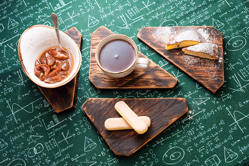 Tea time. Apricot jam, cottage cheese pie and cup of tea on wooden boards. Mathematical formulas on tablecloth background.