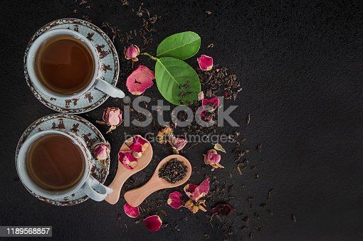 Tea time concept. Two cups of tea, dry rose flowers, tea on the black background. Flat lay, copy space