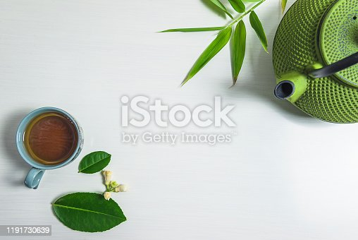 Cup of tea, leaf, cast iron teapot on the white background. Copy space, flat lay