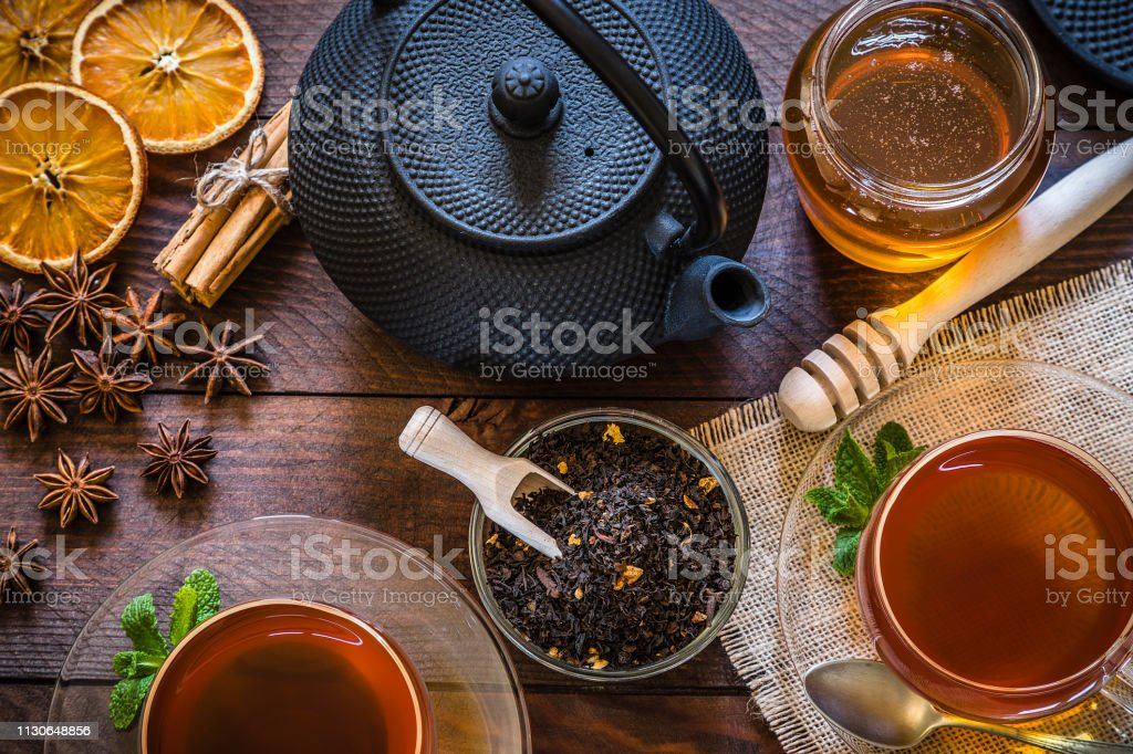 Top view of a rustic wooden table with two tea cups, a teapot and a...