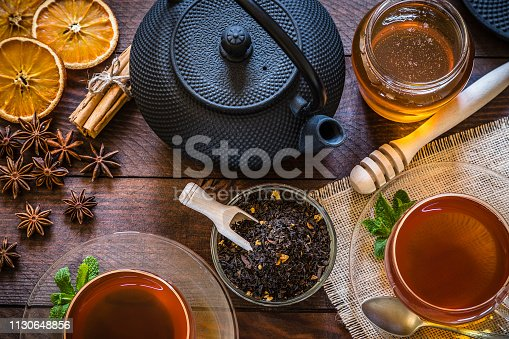 Top view of a rustic wooden table with two tea cups, a teapot and a crystal bowl filled with dried black tea, a honey jar with honey dipper and some ingredients like cinnamon sticks, anise and dried orange for preparing tasty tea. Low key DSLR photo taken with Canon EOS 6D Mark II and Canon EF 24-105 mm f/4L