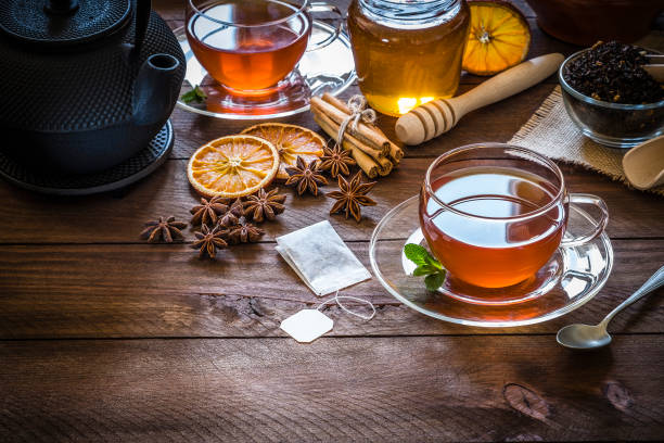 tea time: cup of tea, cinnamon sticks, anise, dried orange on wooden table - tea leaf stock photos and pictures