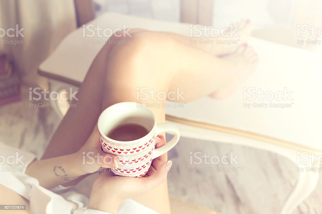 tea time, relaxed woman drinking a tea at home stock photo