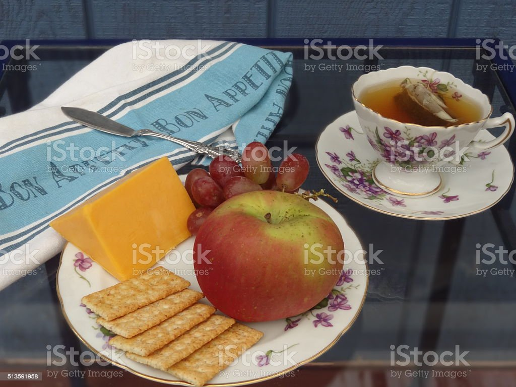 Tea time with cheese crackers and fruit stock photo
