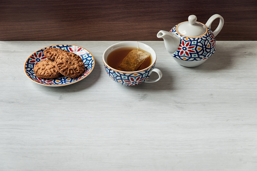 Tea time with homemade whole wheat biscuits on white wooden background