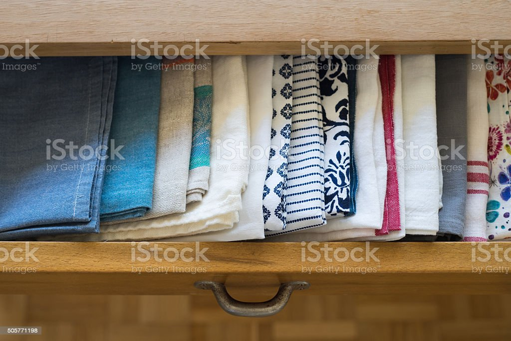 Tea towels arranged in a drawer of dining table stock photo