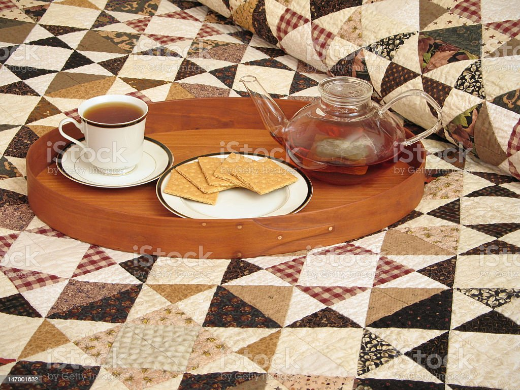 Tea tray on bed with handmade quilt royalty-free stock photo