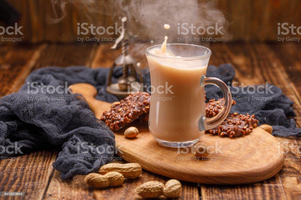 Thé avec des biscuits dans une coupe en verre avec une éclaboussure. Servons le petit déjeuner sur une magnifique planche avec un noyer patiné en arrière-plan. Une tasse de fumer du thé dans un fond en bois. - Photo