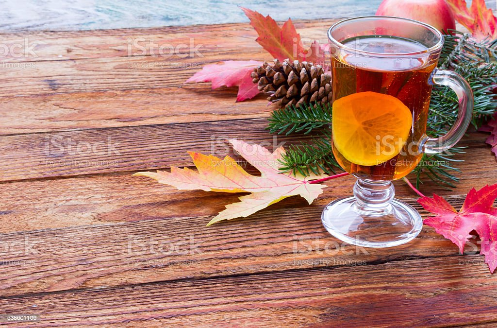 tea with cinnamon and lemon and red autumn leaves stock photo
