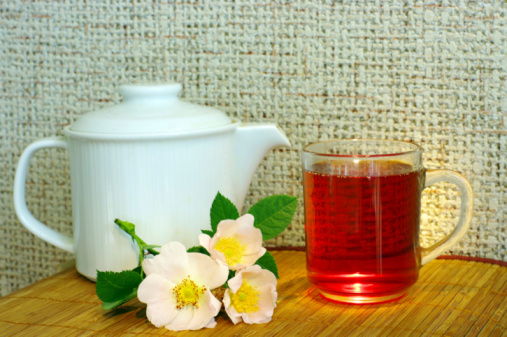tea with dog-rose flowers and white teapot
