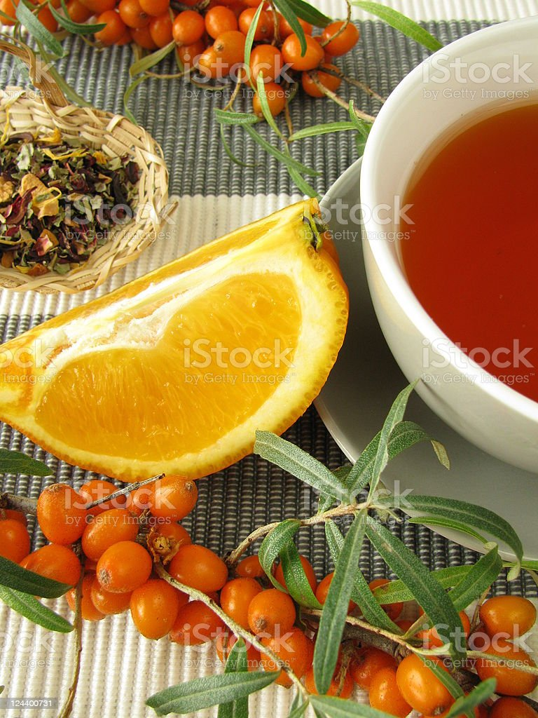 Tea with fruits of sea buckthorn and oranges stock photo