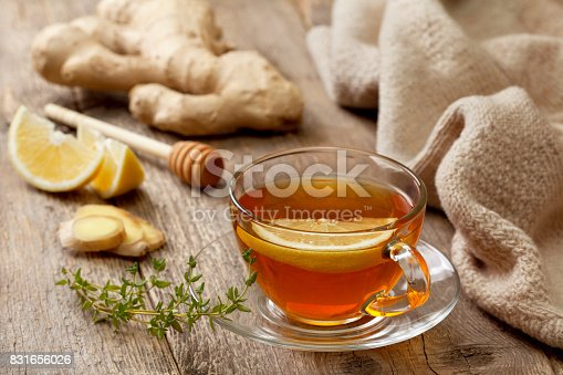 tea with ginger, lemon and thyme on old wooden background