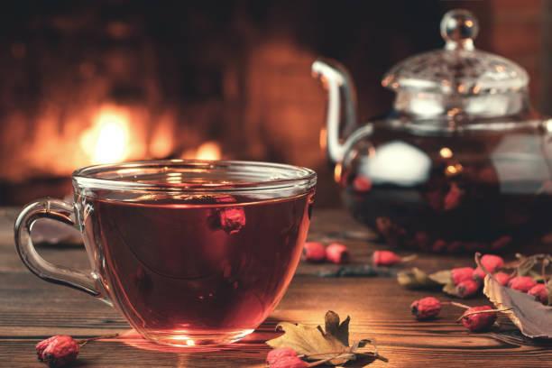 Tee mit Weißdorn in einer Glastasse und Teekanne auf einem Holztisch in einem Zimmer mit einem brennenden Kamin, Nahaufnahme – Foto