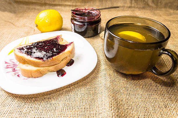 tea with lemon and bitten sandwich. - ingwermarmelade stock-fotos und bilder