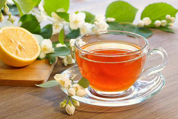 tea with lemon and branches of a blooming jasmine - jasmin party stock-fotos und bilder