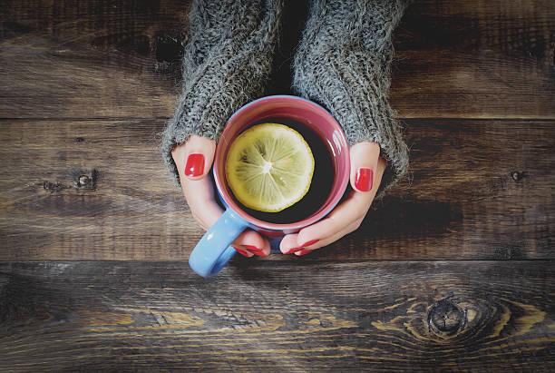 tea with lemon, hand in sweater. top view - herbst nagellack stock-fotos und bilder
