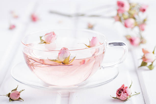 tee mit rosenblüten in einen glas-becher - rosen tee stock-fotos und bilder