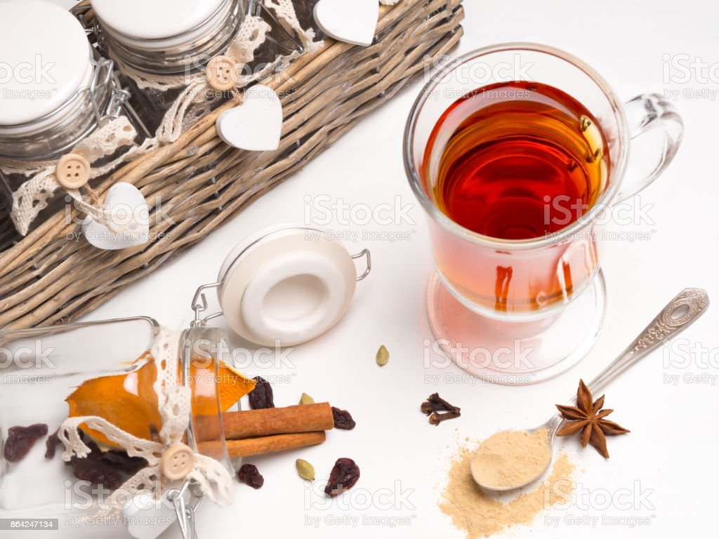 Tea with spices in a glass mug on a white background. Next basket with jars and spices: cinnamon, cardamom, orange, cloves. Spoon with ginger. royalty-free stock photo
