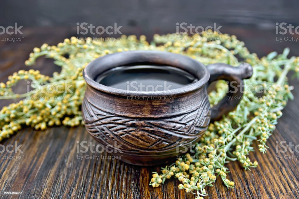 Tea with wormwood in cup on board royalty-free stock photo