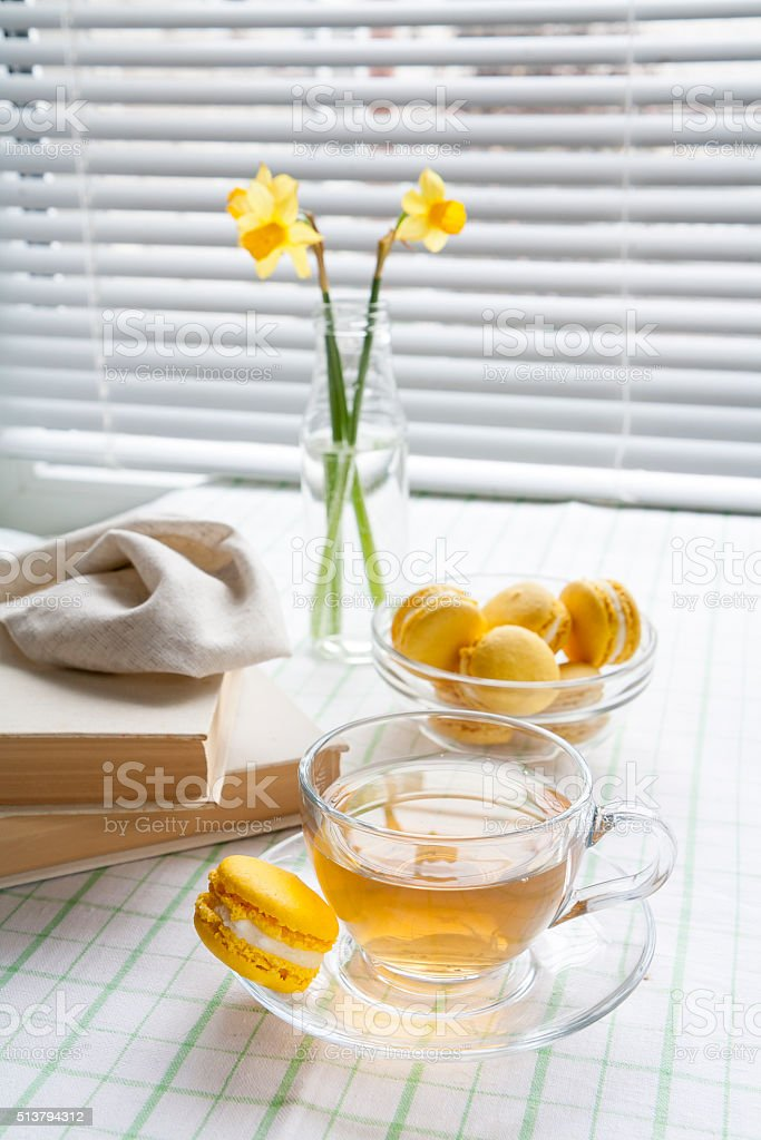 Tea, yellow tulips and daffodils, old books and lemon macaroons stock photo
