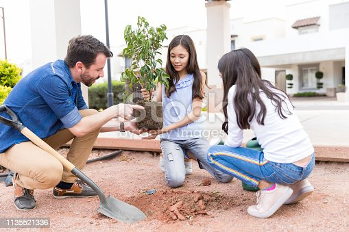 Handsome man teaching gardening to daughters in park on Earth Day