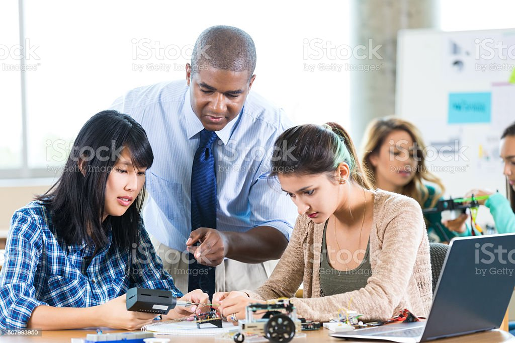 Teacher advises students in STEM high school stock photo