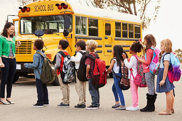teacher and a group of elementary school kids at a - school buses stock pictures, royalty-free photos & images